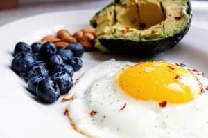 keto 101 egg avocado nuts and blueberries on plate